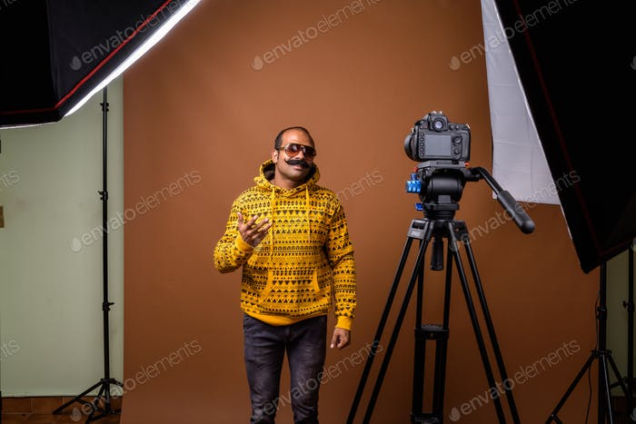 Portrait of Indian man with mustache wearing sunglasses while vlogging