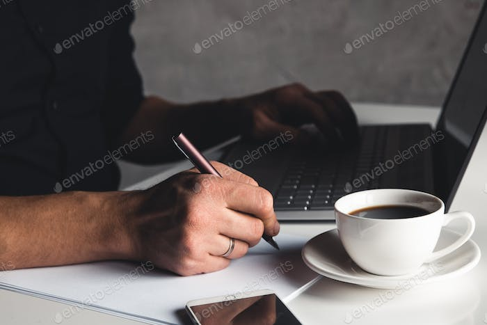 A man types on a laptop, business concept, glasses, a cup of coffee and a pen on a gray background