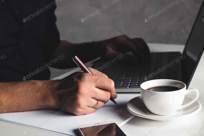 Ein Mann tibt auf einem Laptop, Business-Konzept, Brille, eine Tasse Kaffee und einen Stift auf einem grauen Hintergrund