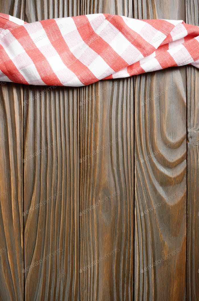 Rote karierte Serviette auf braunem Küchentisch aus Holz mit Kopierraum. Ansicht von oben