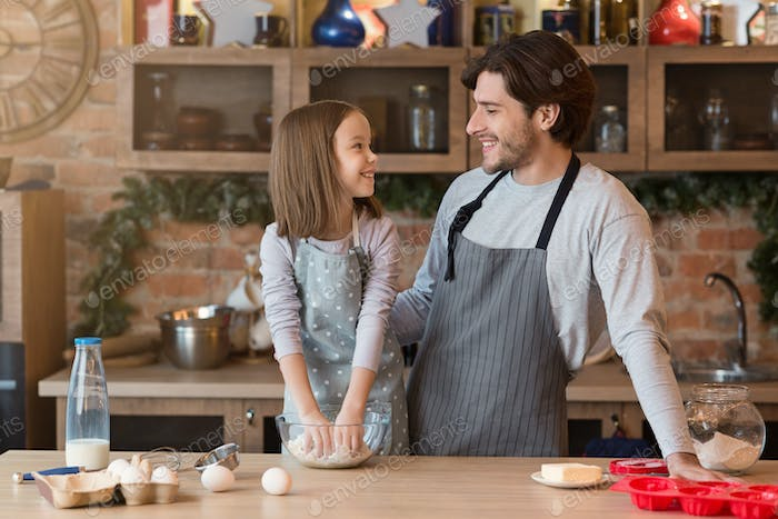 Happy father and little daughter baking pie in kitchen together, kneading dough