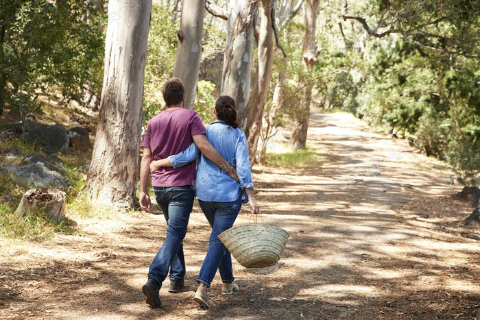 Rear View Of Romantic Couple Hiking Along Forest Path