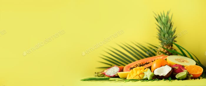 Assortment of exotic fruits on yellow background. Banner. Detox, vegan food, summer concept. Papaya