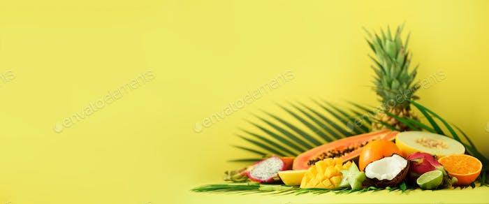Sortiment von exotischen Früchten auf gelbem Hintergrund. Banner. Detox, veganes Essen, Sommerkonzept Papaya