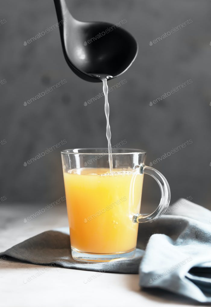 Pouring Homemade Beef Bone Broth in Glasses on a gray concrete background
