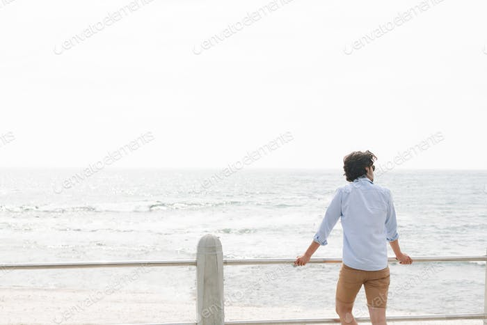 Young man standing near sea side at promenade on a sunny day