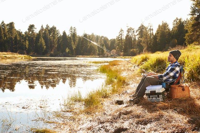 Афро-американский человек Рыбалка по озеру