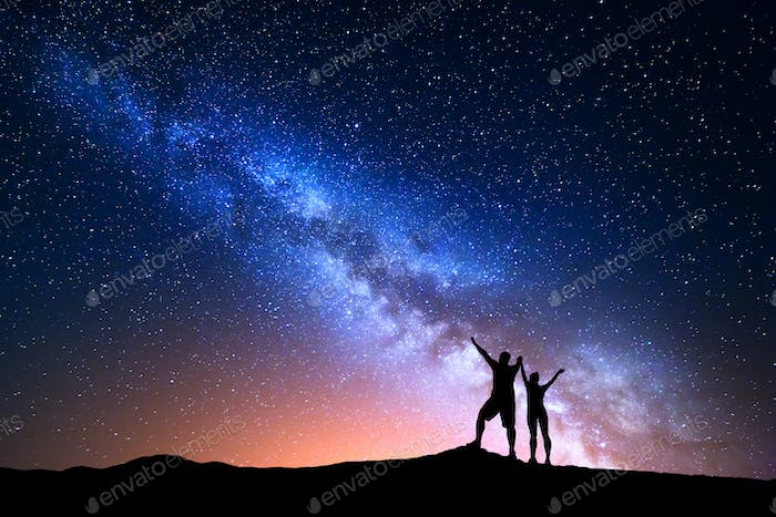 Milky Way and silhouette of happy people