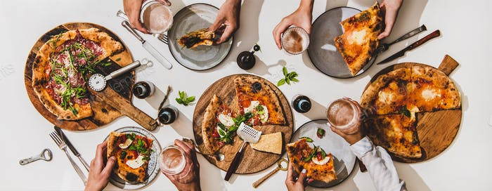Flat-lay of pizzas, lager beer and peoples hands with glasses