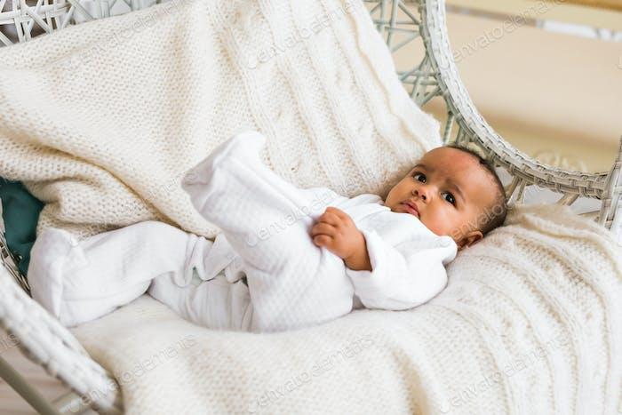 adorable african american baby boy indoors lying