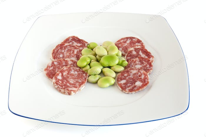 dish with fava beans and salami slices