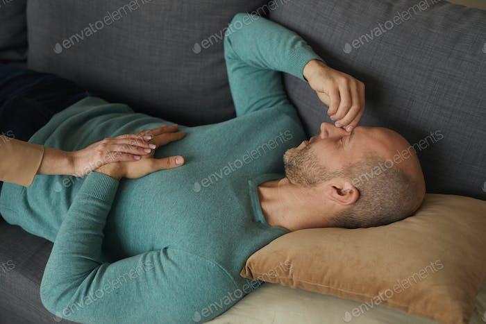 Worried man lying on sofa
