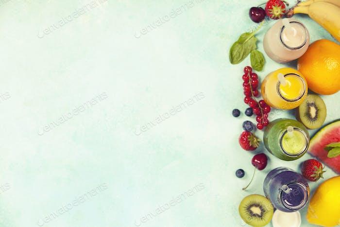 Frische Säfte oder Smoothies mit Obst und Gemüse auf blauem Bac
