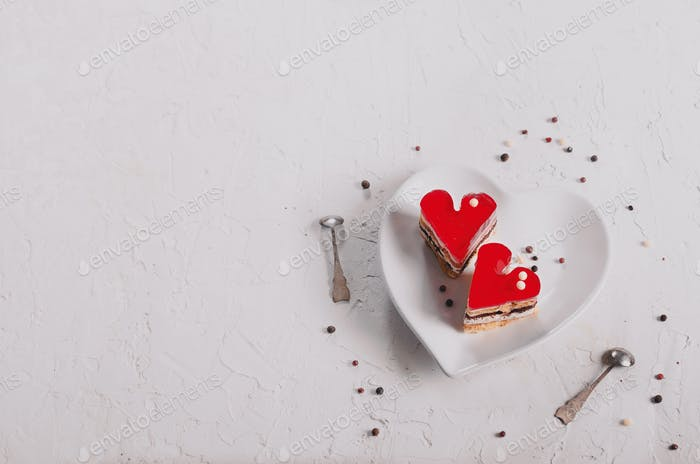Two jelly heart-shaped cakes on white concrete background. Free space for your text. Toned effect