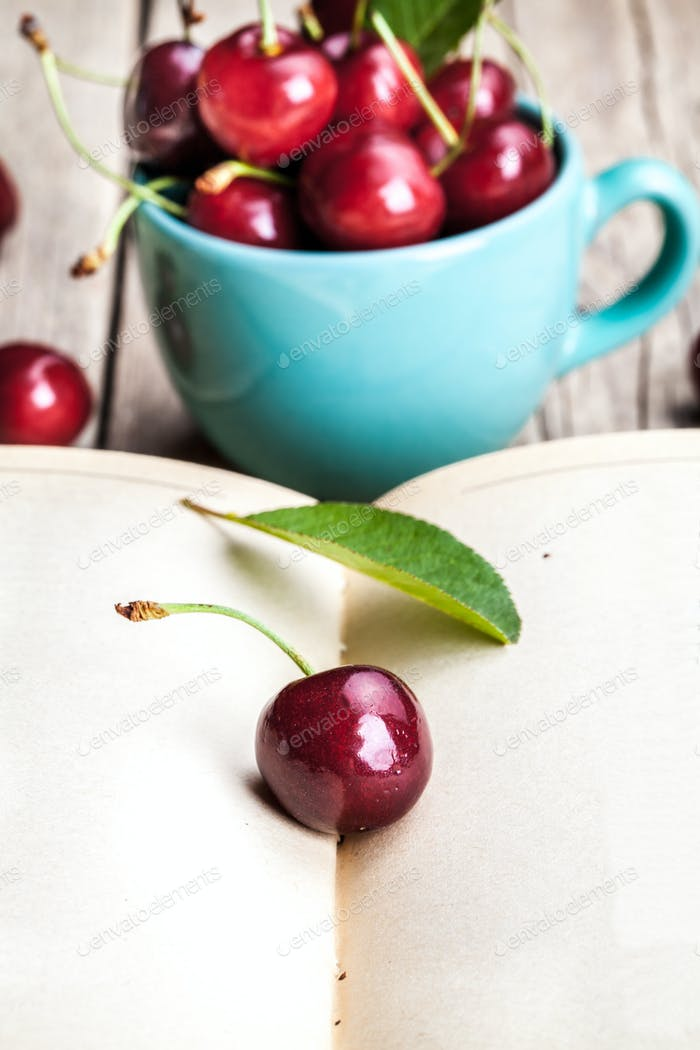 Cherry in the beautiful turquoise cup and old book on a wooden table. Fruit, education