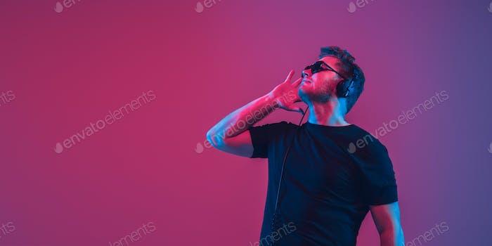Young caucasian musician singing, dancing in neon light, flyer