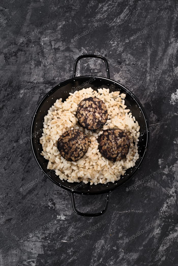 vertical shot of stewed rice with blood sausage on a dark marbled background