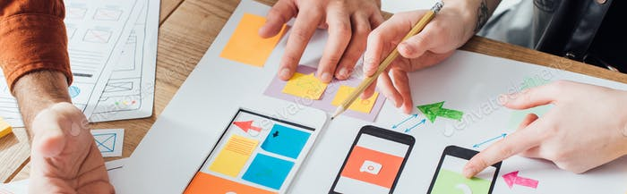 Cropped view of designers creative user experience design of mobile website with layouts on table,