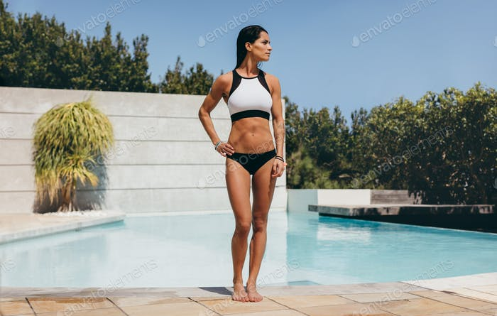 Fit young woman in swimwear standing by a swimming pool