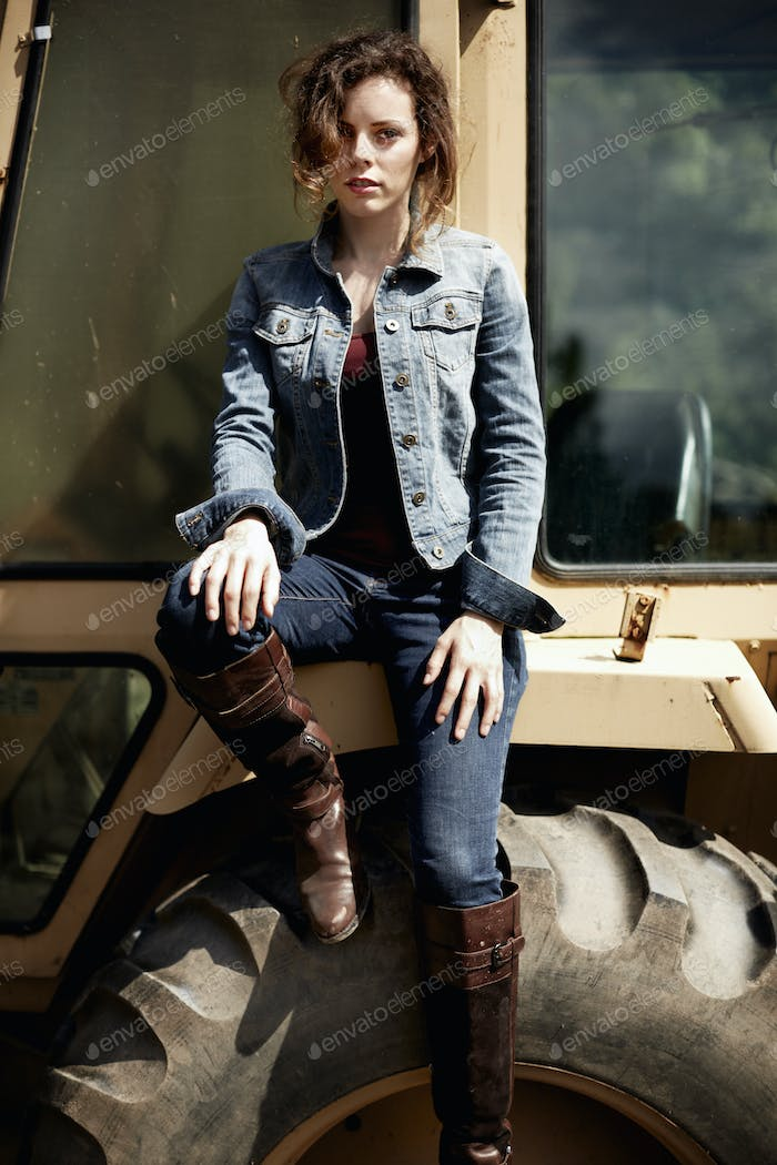 A young woman in denim jacket and boots on the hood of a tractor.