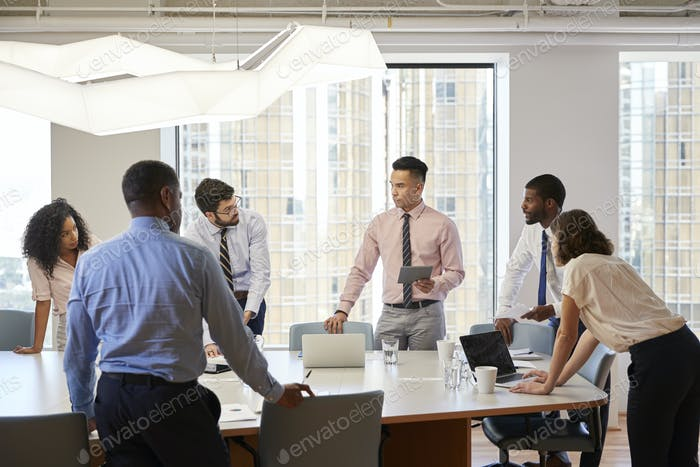 Group Of Business Professionals Standing At Meeting Around Table In Modern Office