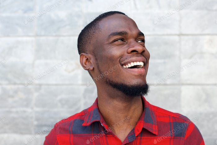 Happy young african american man laughing