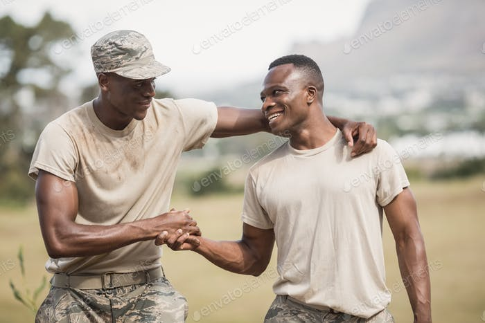 Military soldiers shaking hands during obstacle course