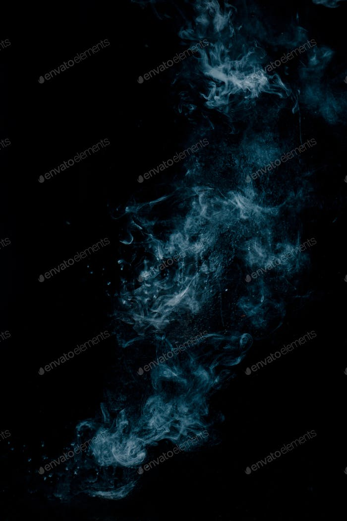 Steam texture from a hot drink on a black background. Blue smoke with copy space.