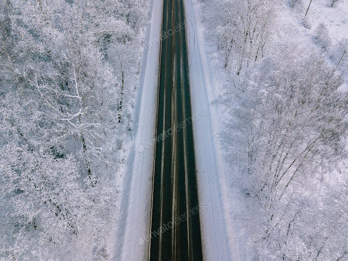 Aerial view of country road going through the beautiful snow covered landscape.