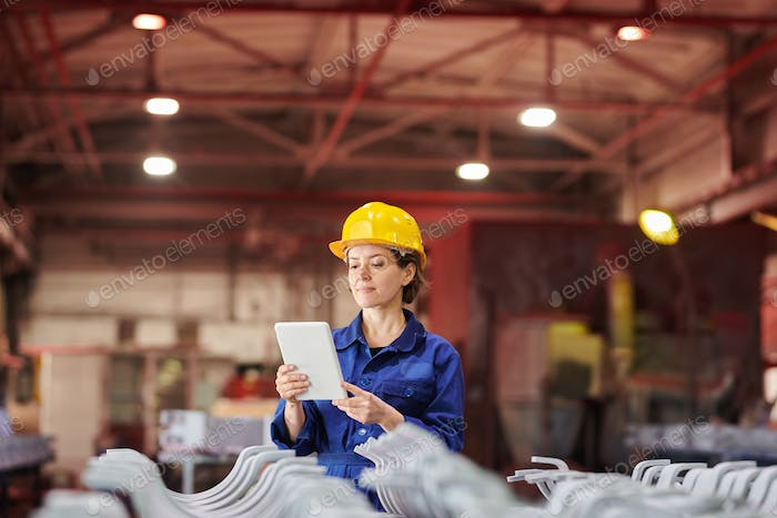 Smiling Woman Using Digital Tablet at Factory