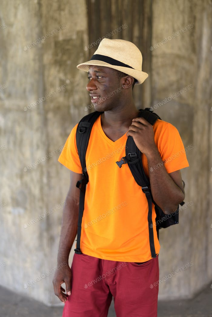 Profile view of young happy black African tourist man smiling