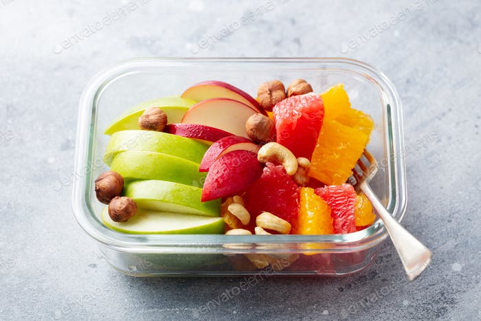 Fruits Salad and Nuts in a Glass Container. Healthy Eating. Grey Background.