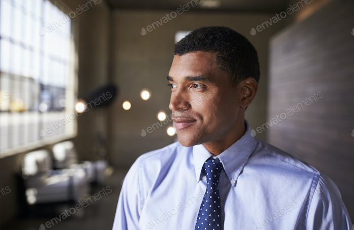 Mixed race businessman looking away smiling, close up