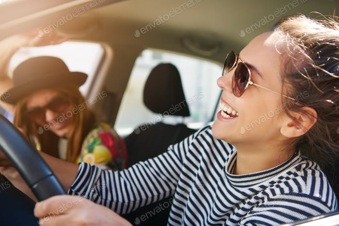 Attractive woman laughing as she drives a car
