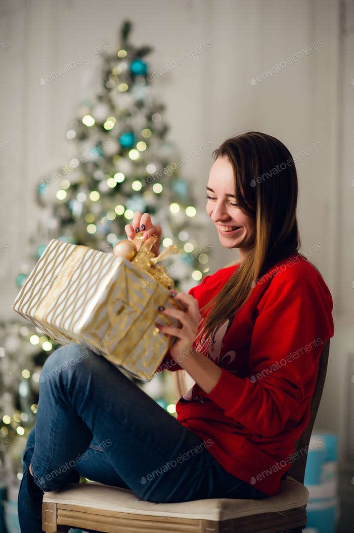 holidays, celebration and people concept - smiling woman wearing red sweather and jeans holding gold