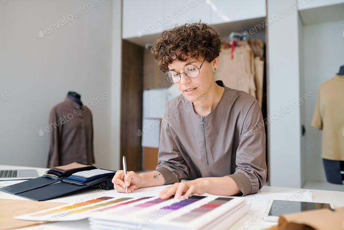 Young businesswoman looking through collectioln of textile samples