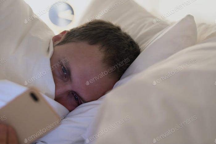 sueño cansado macho acostado en la cama debajo de la manta usando el teléfono inteligente a altas horas de la noche