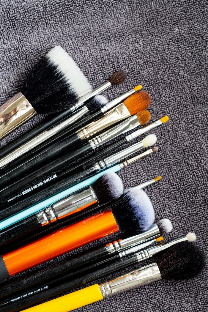 High angle close up of a selection of make-up brushes in various shapes ad sizes.