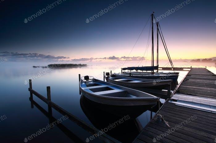 misty sunrise on lake harbor