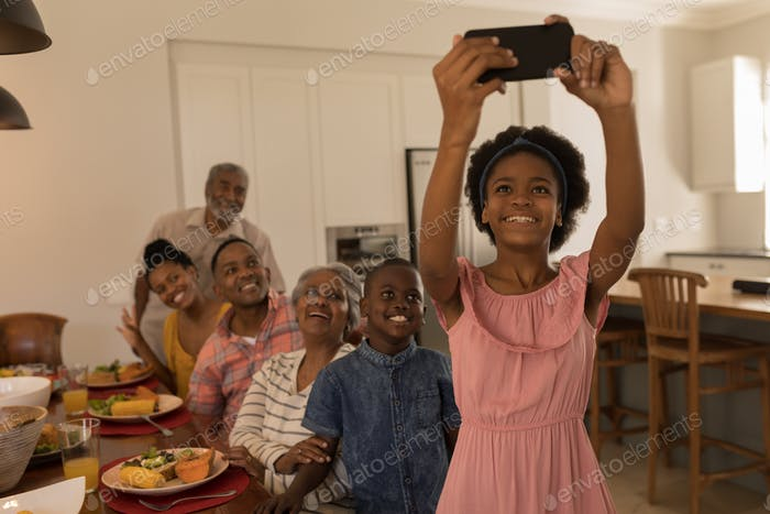 Girl taking selfie with her family sitting at the dining table with her mobile phone at home