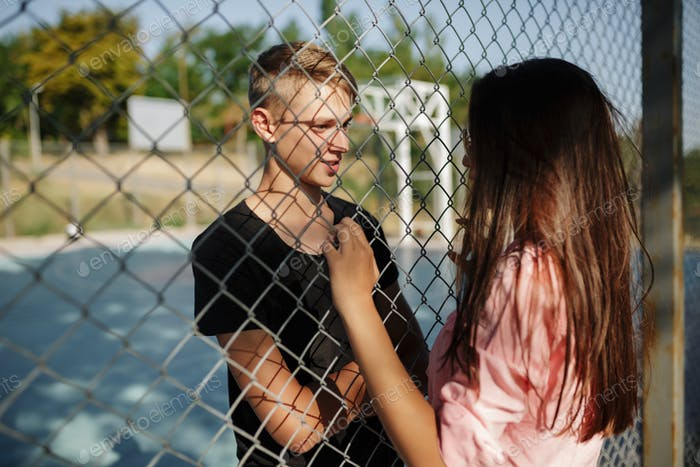 Young thoughtful boy standing on basketball court and dreamily looking at pretty girl with dark hair