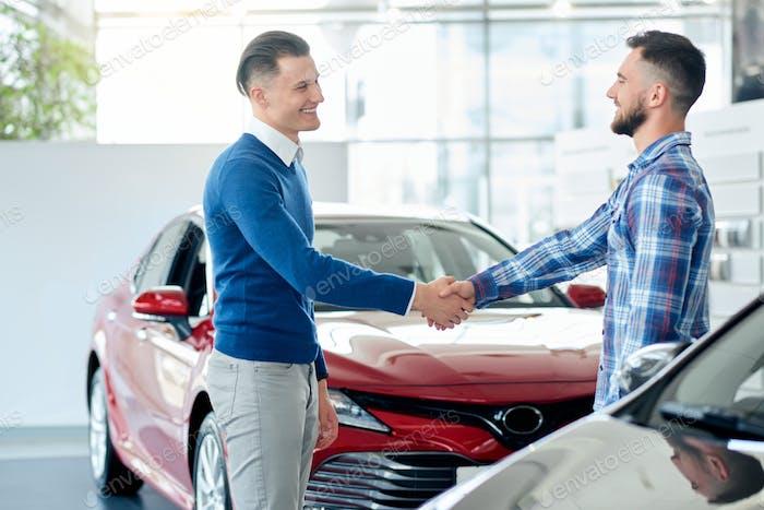 Autohändler und Kunden-Händedruck im Autohaus