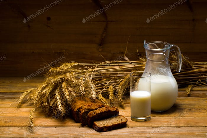Glass jug with milk, mug with milk, a loaf of rye bread, ears on the background of wooden boards