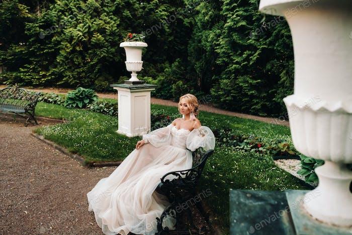 Braut im Garten, Braut sitzt auf einer Bank, Braut sammeln, Morgenbraut, weißes Kleid, anziehen
