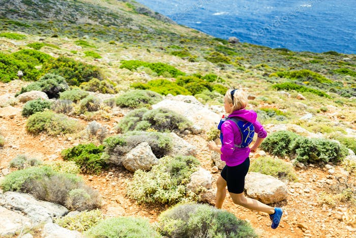Happy woman trail running in beautiful mountains