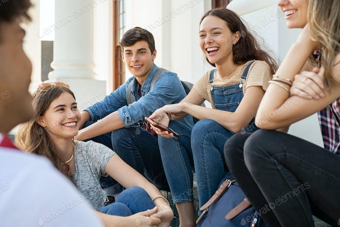 Teenager-Freunde sitzen zusammen und lachen
