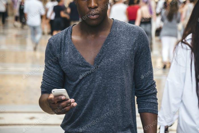 schwarzer junger Mann Blick auf das Telefon in einer Stadt