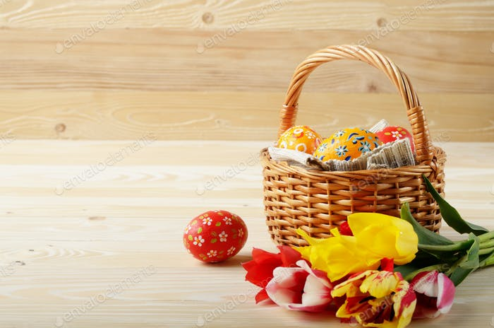 Easter eggs in wicker basket and colorful tulip flowers on woode