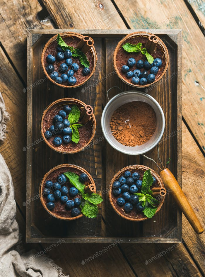Homemade Tiramisu and sieve with cocoa powder in wooden tray