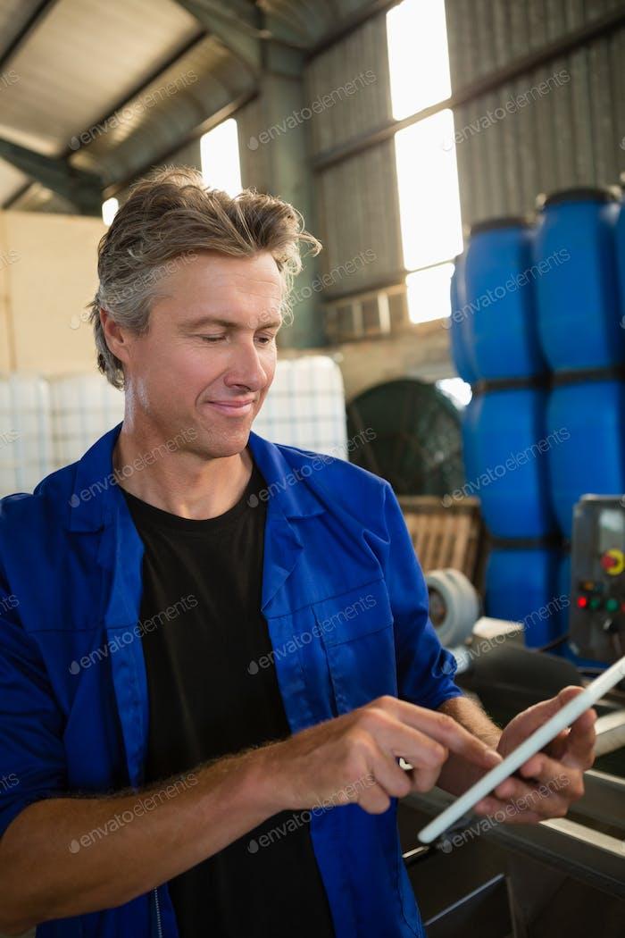 Worker using digital tablet in factory